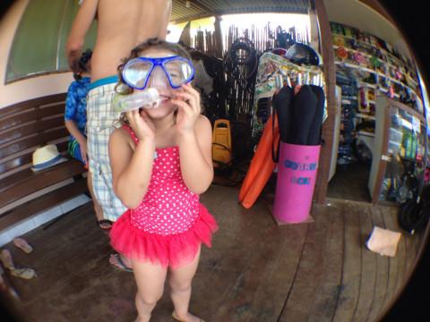 Bianca experimentando uma máscara na loja pra alugar equipamento em frente ao restaurante Xica da Silva - mas no final ela preferiu os óculos, sem snorkel