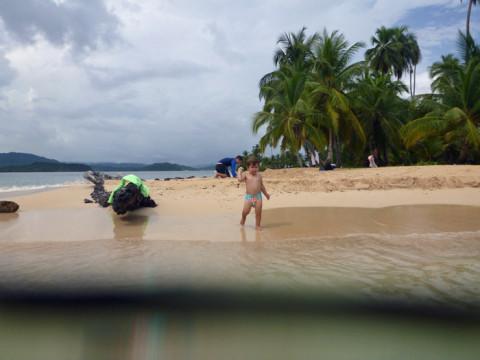 Eric entretido jogando areia na água na ilha Arridup