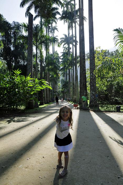 Julia fazendo pose com as palmeiras imperiais ao fundo