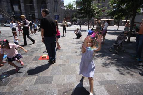 Julia prestes a estourar uma bolha de sabão em frente a Notre Dame de Montreal