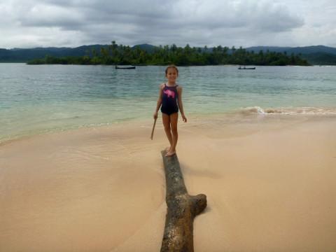 Claro que tinha que escalar o tronco que estava na areia...