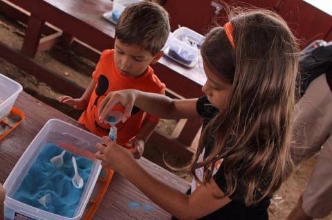 Julia e Eric fazendo arte com areia colorida