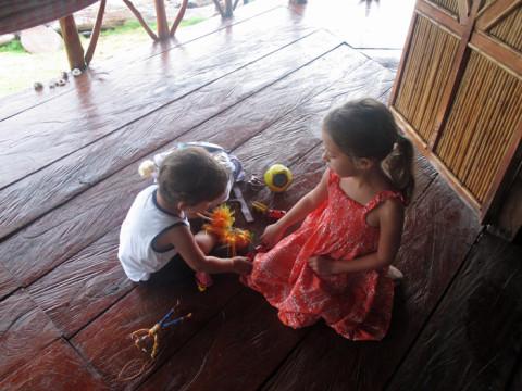Julia e Eric brincando na varanda da cabana esperando a chuva passar