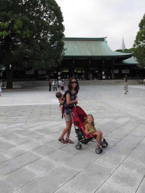 Empurrando a filha no carrinho e com o outro nas costas, no Japão