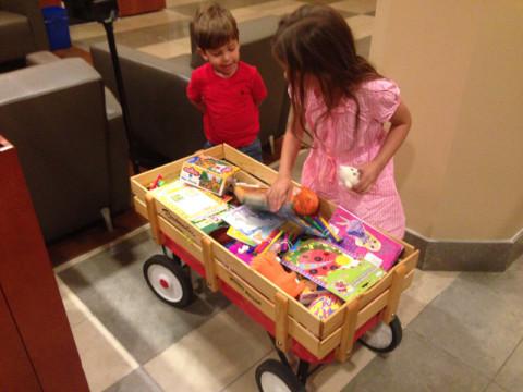 Julia e Eric escolhendo brinquedos no check in