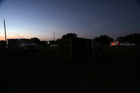 No campo de lançamento dos balões, o nascer do sol começando e a van com o trailer do balão