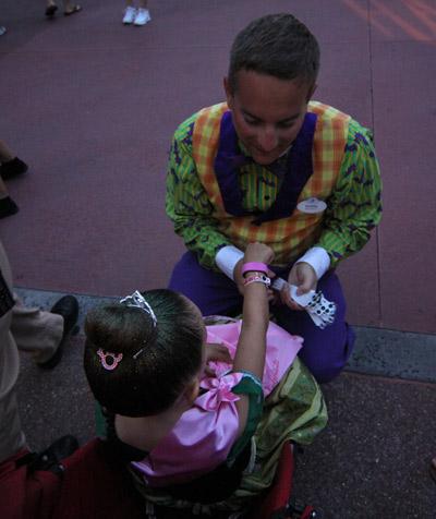 Um funcionário (que na Disney eles chamam de Cast Member) colocando a pulseira de Halloween na Julia