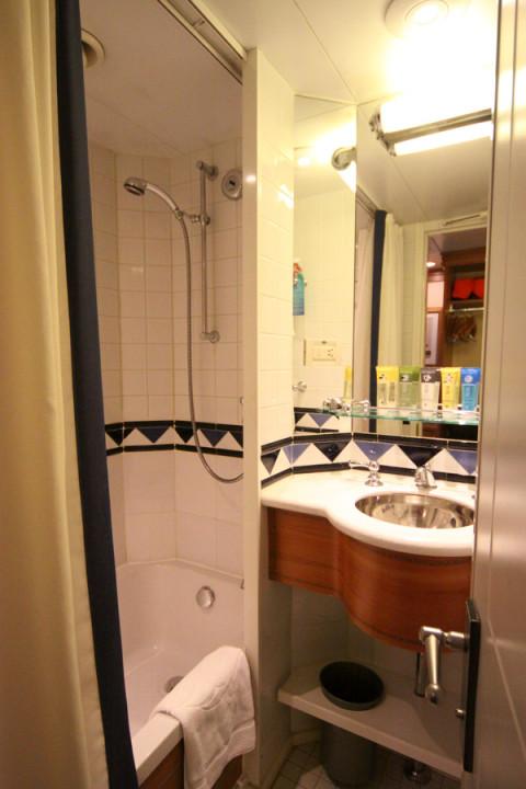 O lado que tem o chuveiro com a banheira e a outra pia, tudo pequeno mas funcional