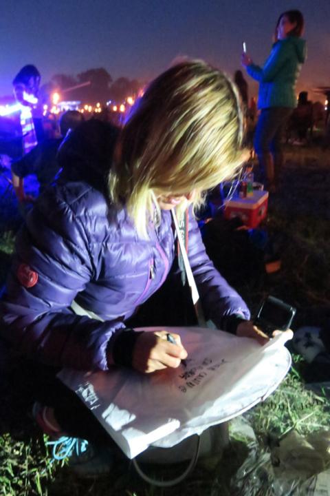 Claudia escrevendo um pedido na sua lanterna