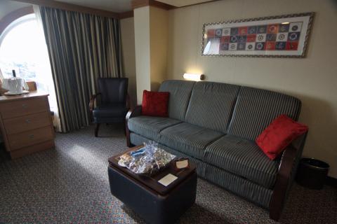 Sofá cama e cadeira de um lado e a mesinha-baú no centro com um presentinho de boas vindas que ganhamos