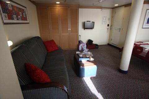 Sofá-cama e closet, TV na parede lá atrás, porta pro corredor e porta do banheiro