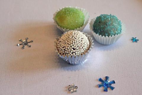 Os docinhos: brigadeiro comum coberto com bolinhas brancas, docinho de nozes coberto com açúcar azul e brigadeiro brancom com açúcar verde