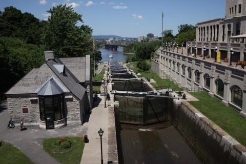 As eclusas do rio Rideau, um barco se aproximando lá embaixo, no rio Ottawa