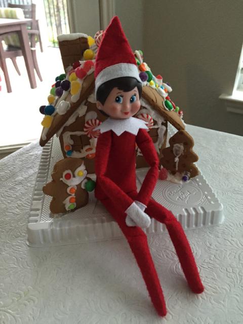 Sentada na frente da casinha de gingerbread que as crianças decoraram
