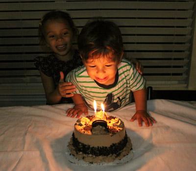 Soprando suas velas, depois de ensaiar muitos Parabéns e Happy Birthdays