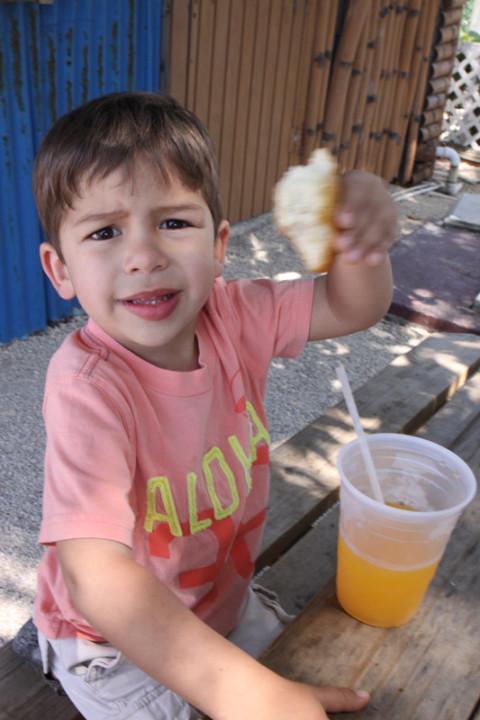 Eric comendo seu fritter e tomando um suco