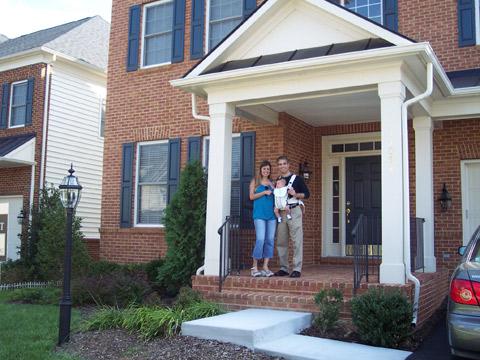 Claudia e a família na frente de uma das casas onde moraram