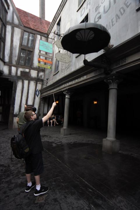 Menino fazendo chover com sua varinha interativa no Beco Diagonal