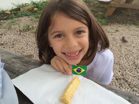 Julia quis tirar uma foto com o aipim e a bandeirinha do Brasil