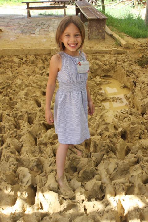 Julia amassando a argila pra fazer os tijolos
