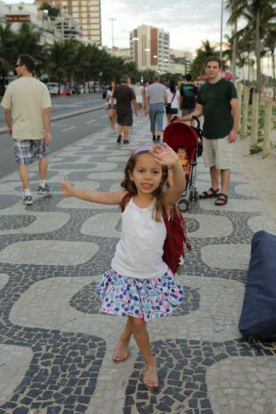 Julia andando e dançando no calçadão de Ipanema
