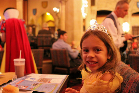 Julia jantando no Cinderella's Royal Table, dentro do Castelo da Cinderela (e a Branca de Neve ao fundo)