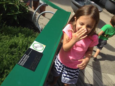 Julia cheirando uma das plantas do Jardim Sensorial