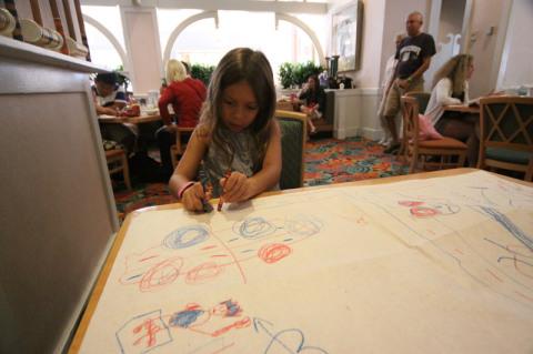 Julia desenhando na mesa