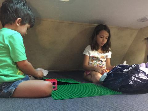 Julia e Eric brincando de Lego na cama em cima da cabine