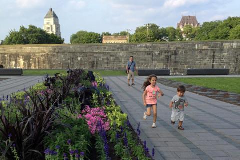 Julia e Eric correndo em frente ao muro da parte antiga de Quebec City