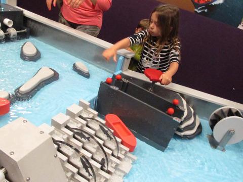 Julia brincando na mesa-represa, muito legal