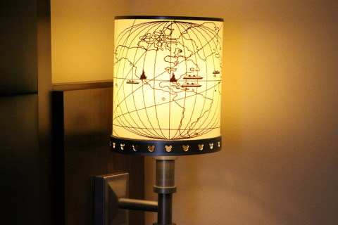 Detalhe da luminária que fica ao lado da cama com as Disneys pelo mapa mundi