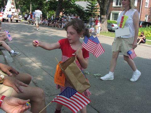 Menina distribuindo doces e bandeiras durante o desfile de 4 de julho em Michigan