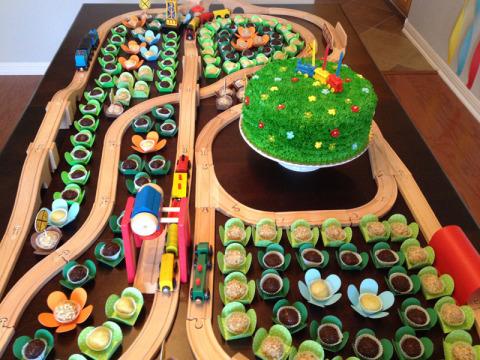A mesa com o bolo e os docinhos no meio dos trilhos