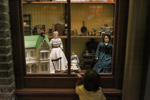 Eric olhando a vitrine de uma loja de brinquedos da época