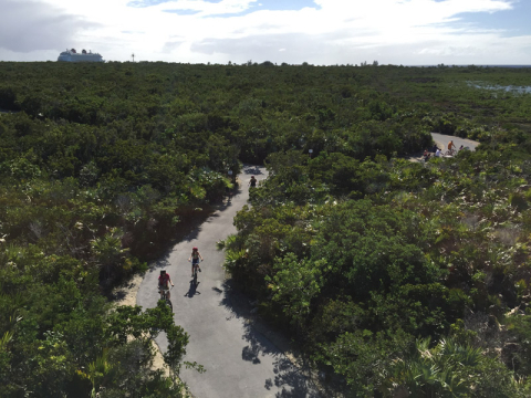 O pessoal pedalando em Castaway Cay e o Disney Dream ao fundo - tiramos essa foto do mirante na trilha