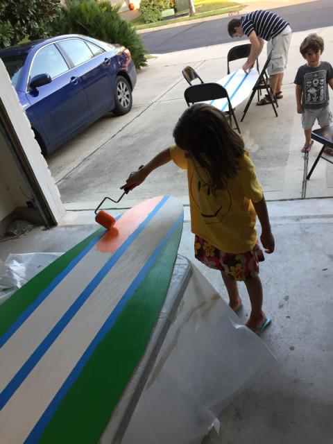 Julia pintando e o Gabe lá atrás colocando fita na outra prancha