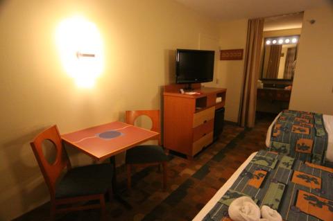 Mesa, cômoda, TV e banheiro no nosso quarto no Pop
