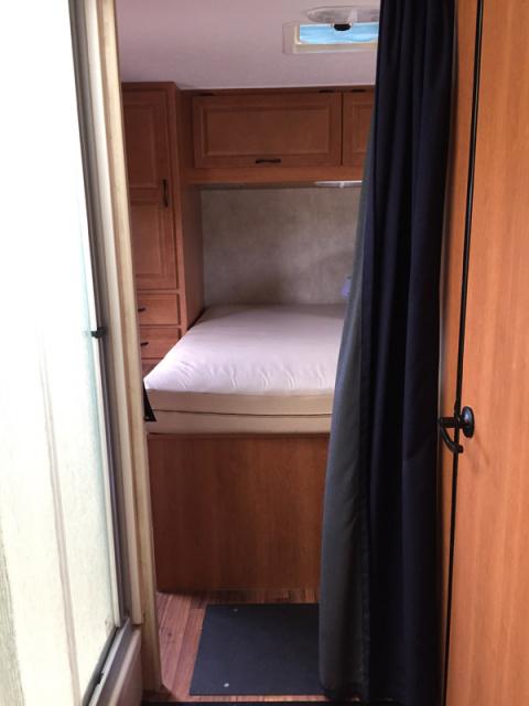Uma outra foto do quarto com o box do chuveiro a esquerda e a porta do banheiro a direita