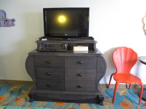 Cômoda (um lado são gavetas e o outro tem uma porta falsa com geladeira ali) e TV no quarto da Pequena Sereia no Art of Animation. Foto: Luciana Misura