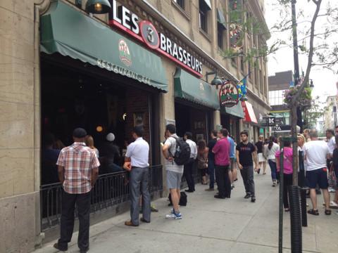 Esse pessoal na calçada estava assistindo a um jogo da Copa do Mundo nas TVs do restaurante!