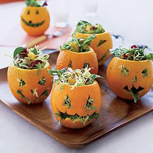 salada dentro de abóboras de Halloween esculpidas em laranjas