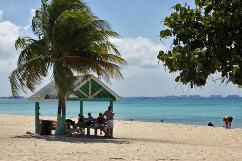 Alguns turistas se escondendo do sol em West Bay Beach