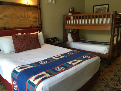 Um quarto com cama de casal e beliche