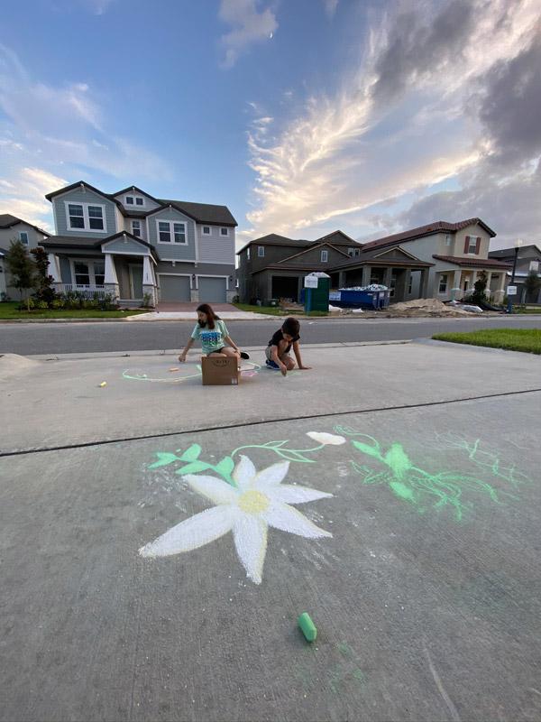 Julia e Eric desenhando com giz na calçada