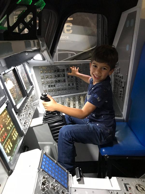 Eric brincando de pilotar um ônibus espacial na réplica do painel de controle