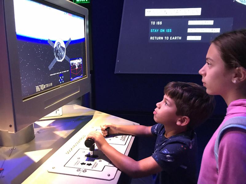 Eric e Julia brincando de pilotar na exposição de Marte