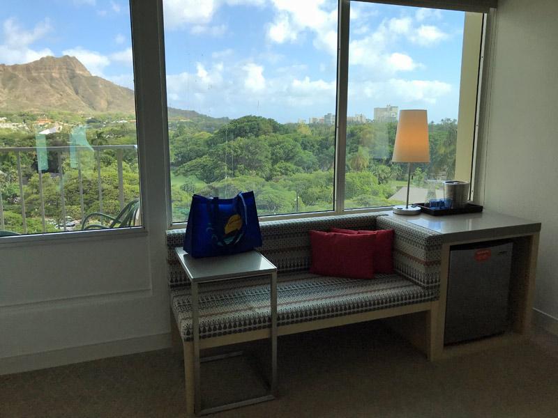 Sofá, mini geladeira, mesinha e a vista linda lá fora